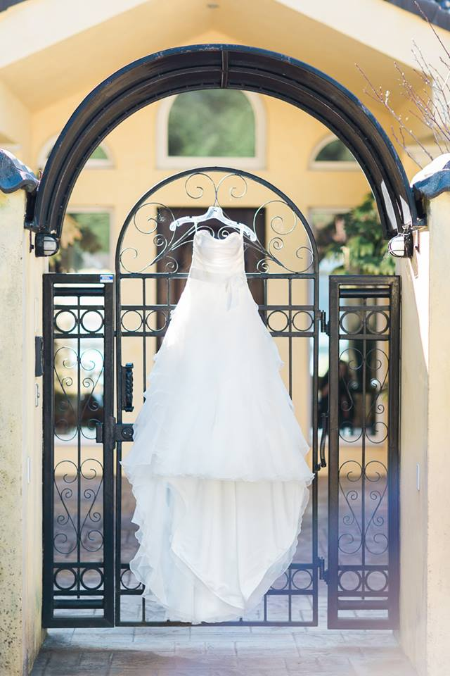 Hazel's gorgeous wedding dress hangs on the outer gates of Casa Christa. Photo credit: Wallpaper Photography