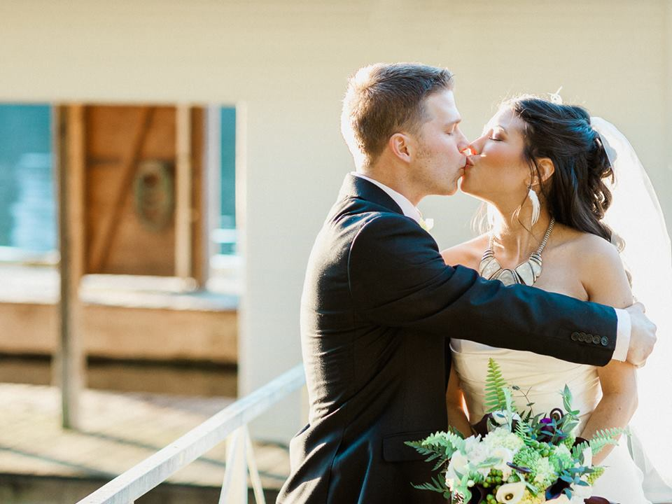 The bride and groom share a kiss in the sunshine. Photo credit: Wallpaper Photography